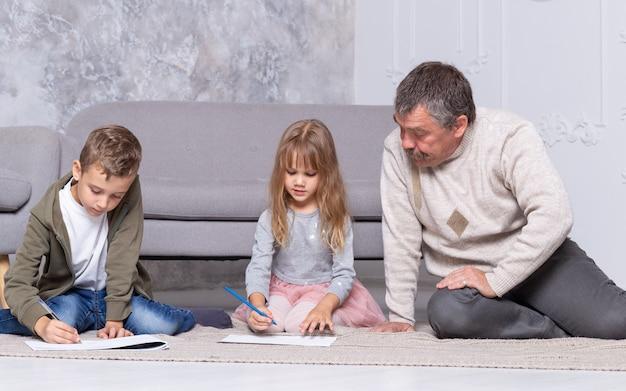 Grootvader en kleinkinderen schilderen samen op de vloer van de woonkamer. volwassen man helpt de kinderen een tekening te maken