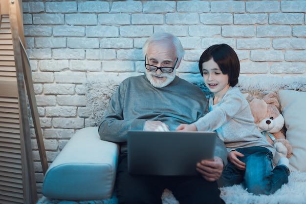 Grootvader en kleinzoon die laptop samen gebruiken