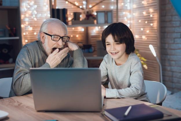 Grootvader en kleinzoon kijken film op laptop
