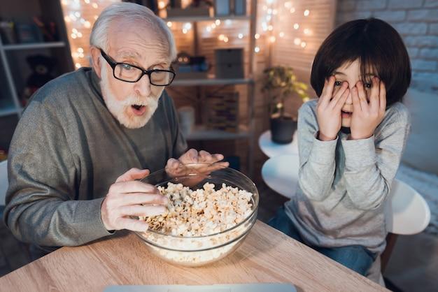 Grootvader en kleinzoon kijken naar enge film