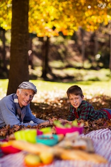 Grootvader en kleinzoon liggend op veld in het najaar