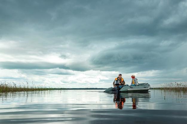 Grootvader en kleinzoon rijden op een motorboot op het meer.