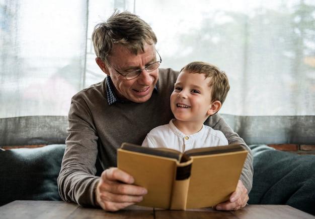 Grootvader en kleinzoon samen een boek lezen
