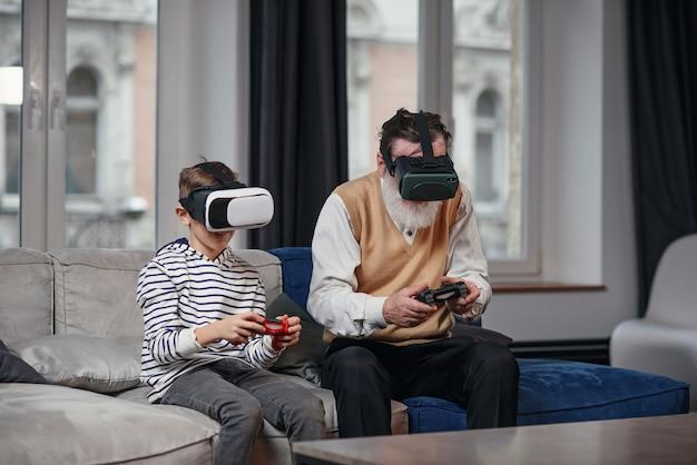 Grootvader en kleinzoon spelen 's nachts thuis videogames op de computer aan tafel