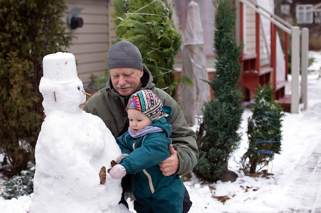 Grootvader en zijn kleine kleindochter maken sneeuwpop in de achtertuin van hun landhuis. winteractiviteiten voor het hele gezin van meerdere generaties.