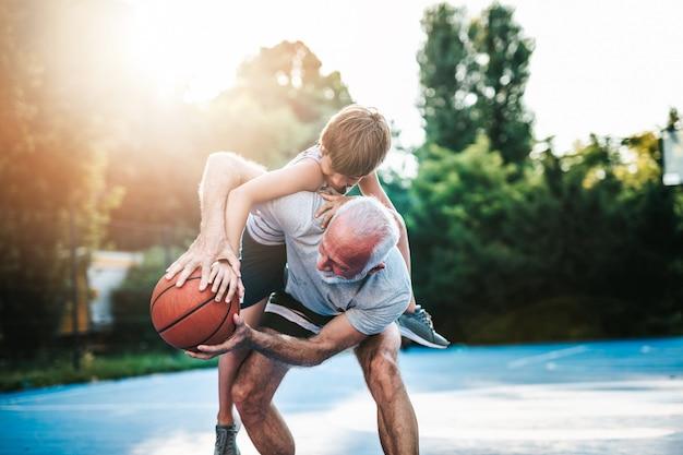 Grootvader en zijn kleinzoon genieten op een mooie zonnige dag en spelen basketbal.