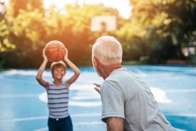 Grootvader en zijn kleinzoon genieten samen op het basketbalveld.