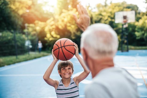 Grootvader en zijn kleinzoon spelen basketbal.