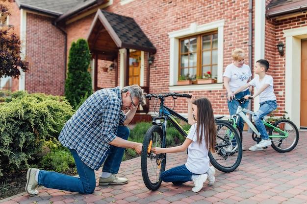 Grootvader in de buurt van zijn huis met kinderen repareert de fiets. fietsmonteur in een werkplaats in het reparatieproces