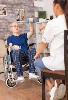 Grootvader in rolstoel die sport doet, bijgestaan door een verpleegster.