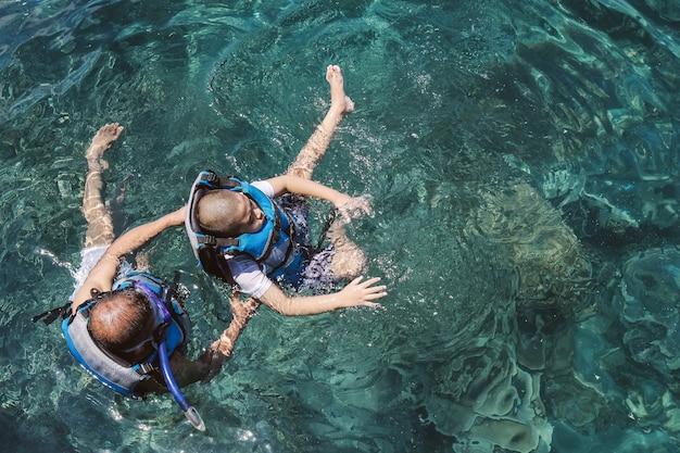 Grootvader leert zijn kleinzoon zwemmen op de oceaan met helder water met reddingsvest