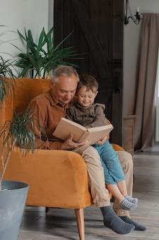 Grootvader leest een boek met kleinzoon thuis