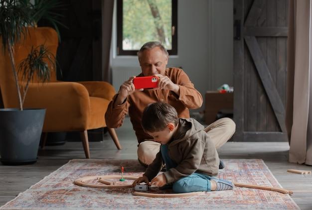 Grootvader maakt een foto terwijl kleinzoon thuis met de trein speelt