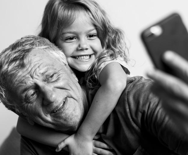 Grootvader maakt een selfie met zijn kleindochter
