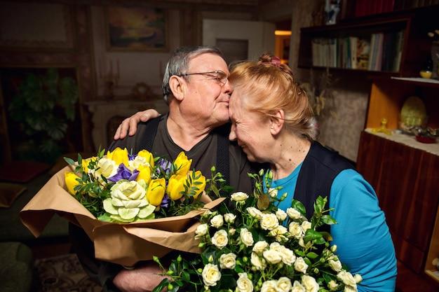 Grootvader met boeketten bloemen feliciteert grootmoeder. bejaarde echtpaar verliefd. gepensioneerden zoenen. familie met pensioen.
