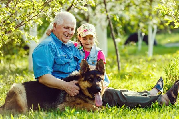 Grootvader met kleindochterhond en een hond in de tuin