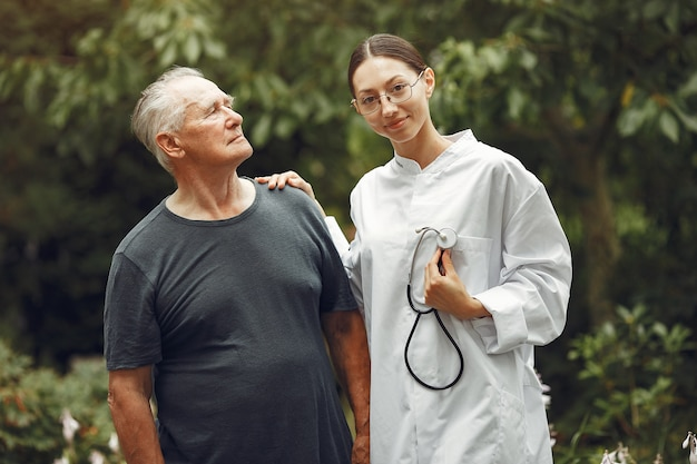 Grootvader met rolstoel bijgestaan door verpleegster buiten. senior man en jonge verzorger in het park.