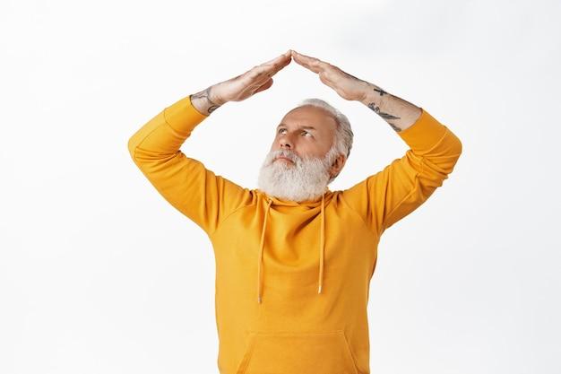 Grootvader met tatoeages die verward naar zijn handen kijkt, een dakgebaar, nadenkend fronsend terwijl hij zijn huis op het dak maakt, staande tegen een witte muur