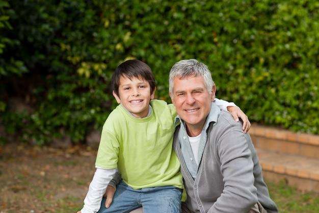 Grootvader met zijn kleinzoon kijken naar de camera in de tuin