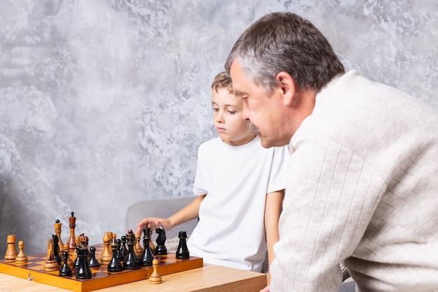 Grootvader schaken met kleinzoon binnen. de jongen en zijn opa zitten op de bank in de woonkamer en denken aan het spel. senior man leert een kind schaken
