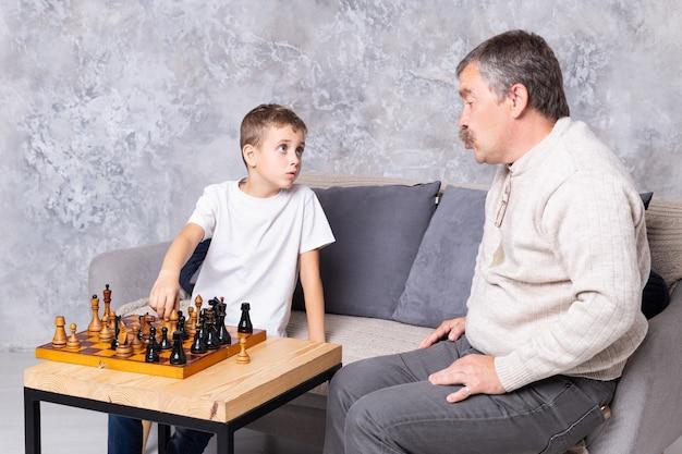 Grootvader schaken met kleinzoon binnen. de jongen en zijn opa zitten op de bank in de woonkamer en praten samen