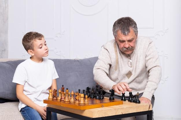 Grootvader schaken met kleinzoon binnen. de jongen en zijn opa zitten op de bank in de woonkamer en spelen