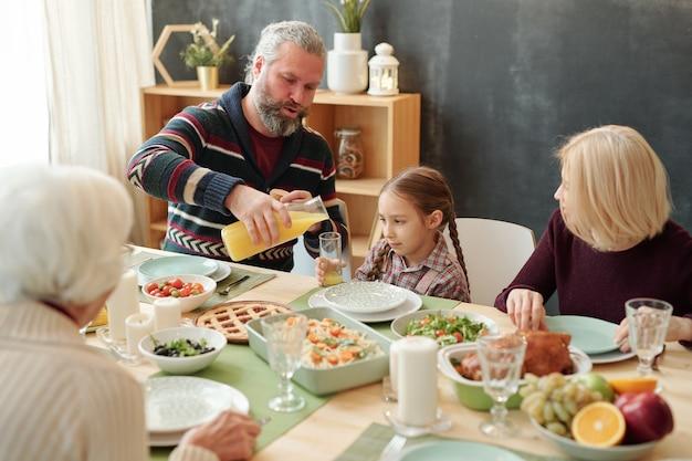 Grootvader sinaasappelsap gieten in glas van zijn schattige kleindochter door feestelijke tafel onder volwassen vrouwen