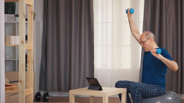 Grootvader training in de woonkamer met halters kijken naar online fitnessprogramma. bejaarde gepensioneerde gezonde opleiding gezondheidszorg sport thuis, fitness activiteit uitoefenen op oudere leeftijd