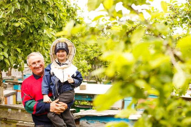 Grootvader van imker en kleinzoon onderzoeken een bijenkorf