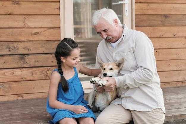 Grootvader zit samen met zijn kleindochter op de veranda met hond buiten