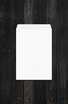 Grote a4 witte enveloppe mockup sjabloon geïsoleerd op zwarte houten achtergrond