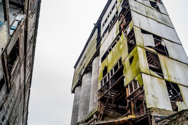 Grote afbrokkelende verlaten fabriek. ruïnes van industriële ondernemingen, fabrieksterreinen verwoest in fabriek als gevolg van economische crisis en aardbeving