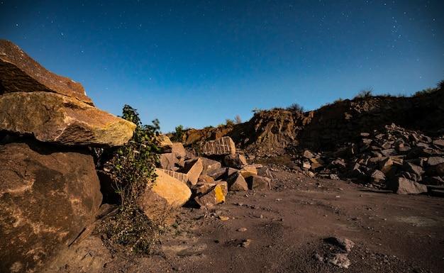 Grote afzettingen van steenmaterialen bij een mijn in de karpaten tegen de achtergrond van de hemel met de maan