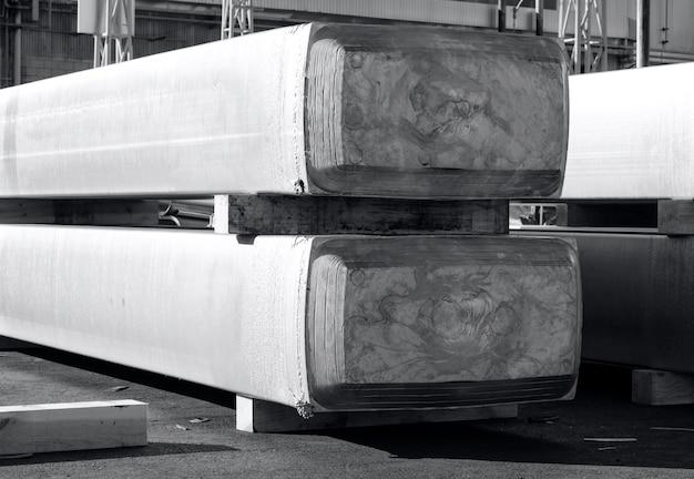 Grote aluminium blokken gestapeld in een werfgieterij, grondstof om te worden verwerkt in een hete molen. foto in zwart-wit met blauwachtige toon