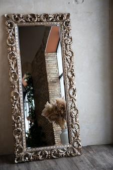 Grote antieke vloerspiegel in het interieur. vintage. mooie spiegellijst.