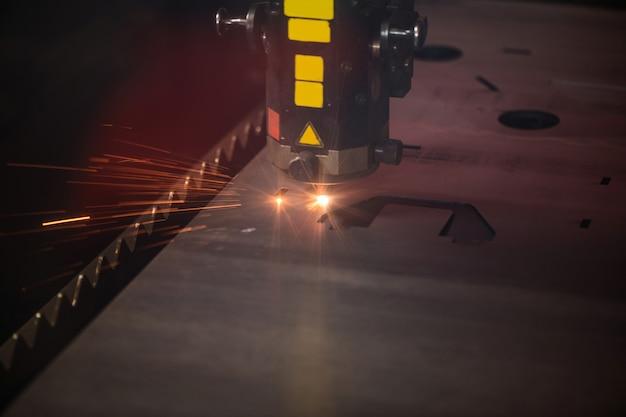 Grote autometrische industriële machine die las- of laserwerkzaamheden uitvoert op een metalen oppervlak in de fabriek