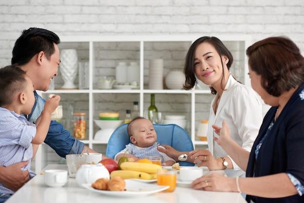 Grote aziatische familie die ontbijt heeft