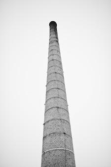 Grote bakstenen toren zonder rook tegen mistige hemel.
