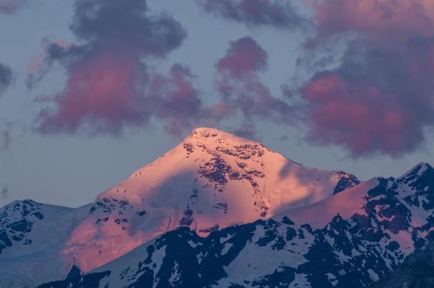 Grote bergen in wolken op zonsondergang