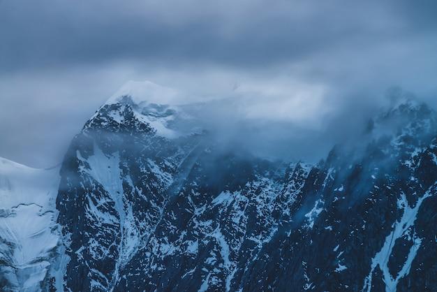 Grote bergtop met sneeuw in bewolkte hemel in schemering.