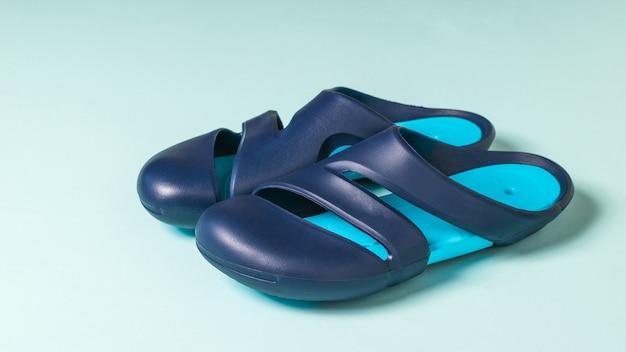 Grote blauwe heren teenslippers voor in het zwembad. rubberen schoenen.