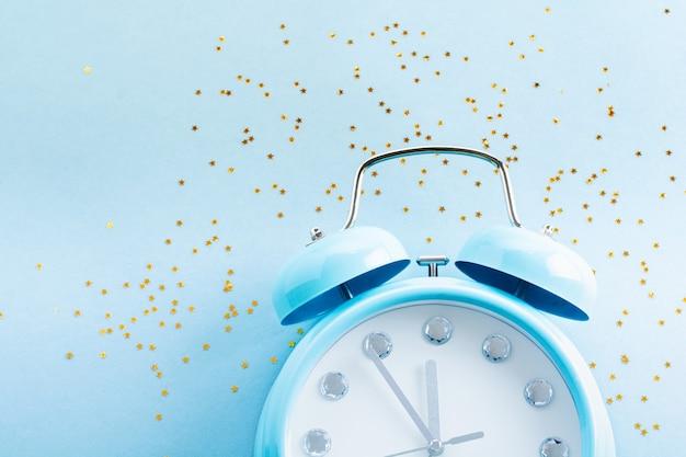 Grote blauwe wekker liggend en oppervlak weergegeven: 23 uur en 55 minuten met glanzende confetti sterren op lichtblauw oppervlak