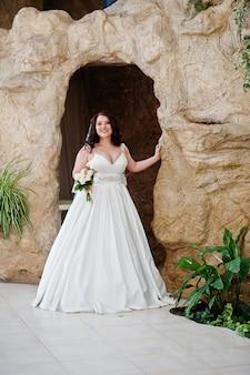 Grote borsten donkerbruine bruid met huwelijksboeket die bij het verfraaide hol van de huwelijkszaal achtergrond wordt gesteld