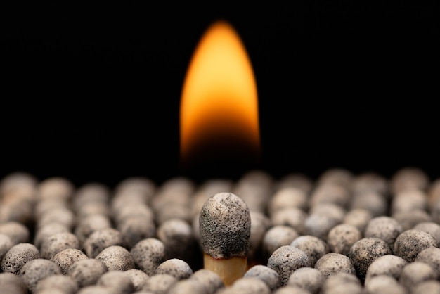 Grote brandende lucifer tussen andere burnet en gedoofde lucifers