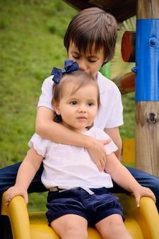 Grote broer knuffelde en gaf hem een kus op het hoofd aan zijn jongere zus tijdens het spelen in een park.