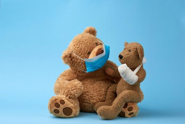 Grote bruine teddybeer zit in een medisch masker, in zijn handen houdt hij een klein speeltje