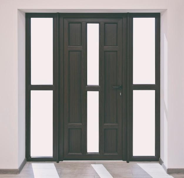 Grote bruine toegangsdeuren met witte ruimtes in plaats van glas