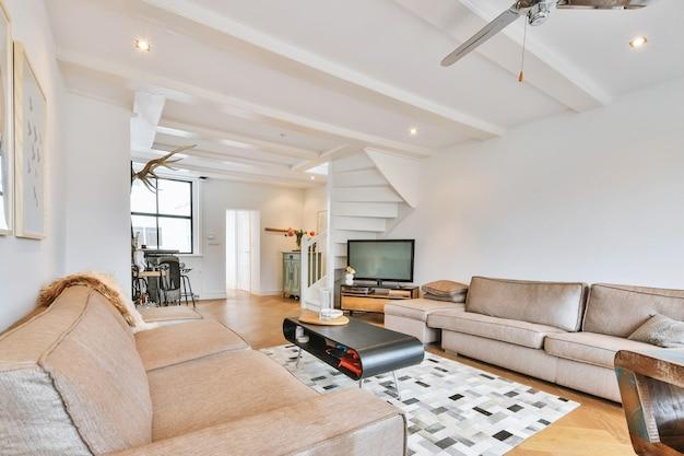 Grote comfortabele banken in wit gekleurde woonkamer met tapijt op parketvloer in modern appartement