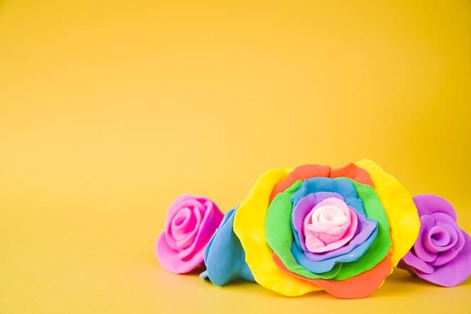 Grote creatieve mooie roos gemaakt met klei op gele achtergrond