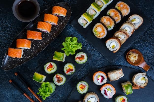 Grote diverse reeks sushi rolt op een zwarte houtskooltribune op een zwarte achtergrond. traditioneel japans eten. bovenaanzicht.